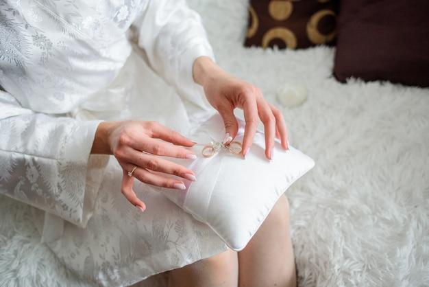 Mariée détient un oreiller avec des anneaux de mariage