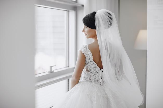 Une mariée élégante et belle à la maison debout près de la fenêtre