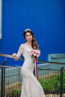 Mariée élégante avec bouquet de fleurs de mariage, jolie femme en robe de mariée. jeune fille en robe blanche monte les escaliers d'une belle maison blanche. heureuse jeune mariée. mariée avec maquillage de mariage