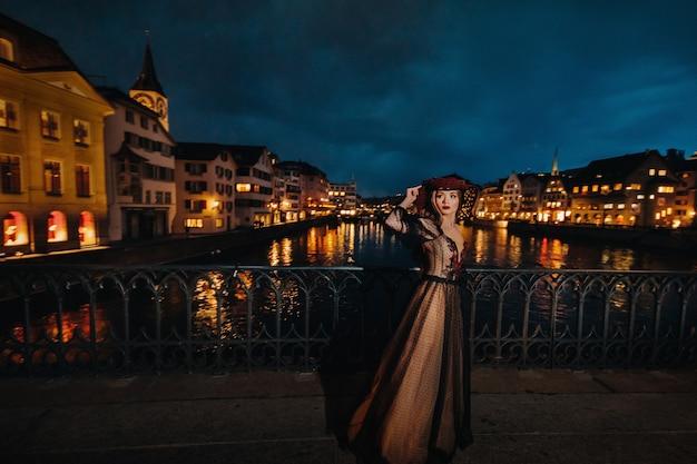 Une mariée élégante dans une robe de mariée noire et un chapeau rouge pose la nuit dans la vieille ville de zurich. portrait d'une jeune fille modèle après le coucher du soleil. séance photo en suisse.