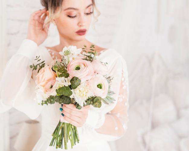 Mariée élégante posant avec son bouquet
