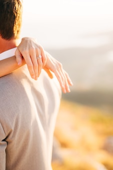 La mariée embrasse le marié les mains de la mariée avec la bague de mariage sur les épaules du marié en gros plan