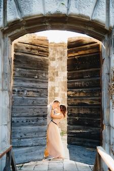 La mariée embrasse le marié en se tenant debout derrière la porte en bois ouverte du château