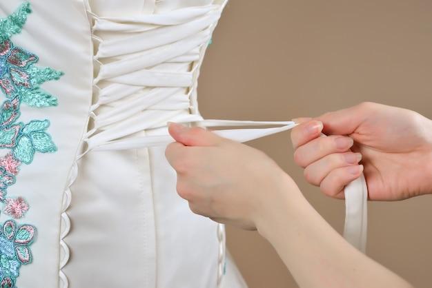 La mariée est aidée à lacer le corset vue de dessus
