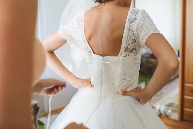 La mariée est aidée à porter une robe de mariée, un corset en dentelle, vue arrière