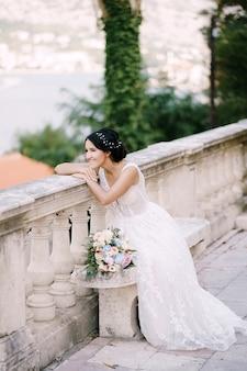 La mariée est assise sur un banc sur un site pittoresque de la vieille ville s'appuie sur la balustrade et sourit