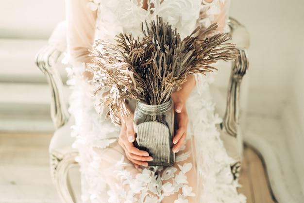 La mariée est assise sur une chaise avec un bouquet inhabituel dans ses mains