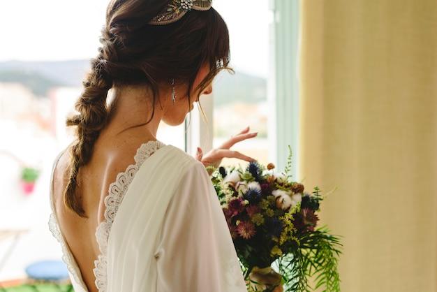 La mariée est de retour avec sa robe de mariée tenant son bouquet.