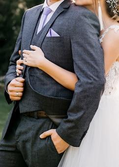 Mariée étreignant le marié par derrière, gros plan