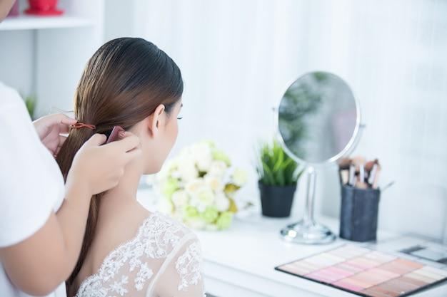 Mariée faire les cheveux avec la robe