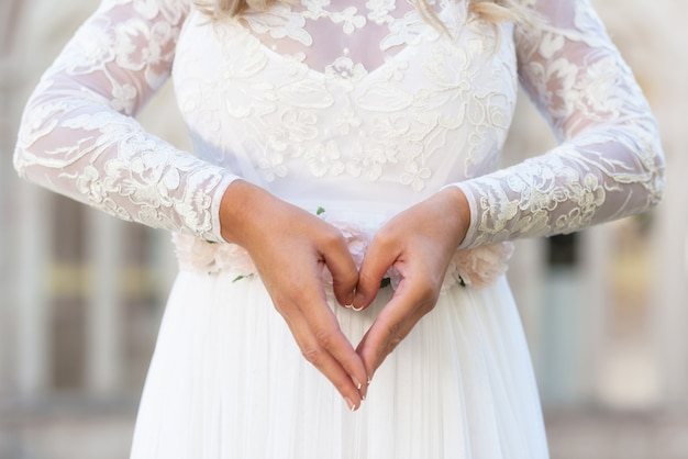 Mariée faisant signe de coeur. concept d'amour