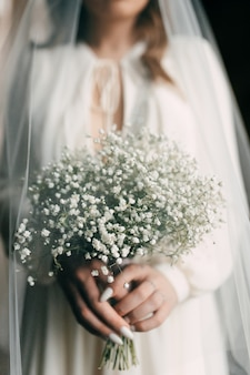 Mariée femme en robe de mariée tenant un bouquet blanc à la main