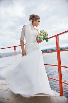 Mariée avec des fleurs dans ses mains, debout dans le vent
