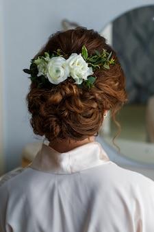 Mariée avec des fleurs naturelles blanches dans ses cheveux
