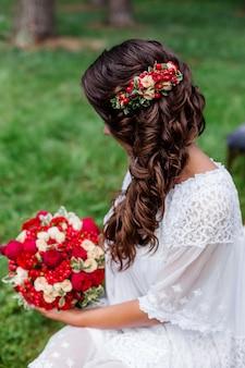 Mariée avec des fleurs naturelles rouges et de la verdure dans ses cheveux