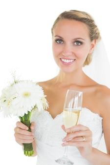 Mariée gaie tenant un bouquet et un verre de champagne