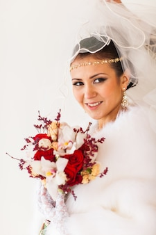 Mariée heureuse avec bouquet et bijoux en diamant en attente pour le marié le jour du mariage d'hiver