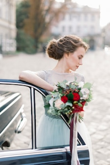 Mariée heureuse élégante debout près de la voiture rétro noire et tenant le bouquet de mariée. bâtiments de la vieille ville sur le fond. moment émotionnel.