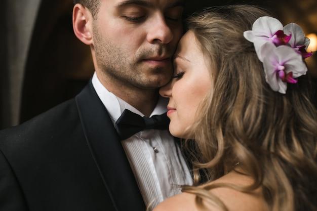 Mariée heureuse avec la tête sur l'épaule de petit ami