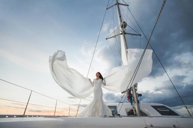 Mariée heureuse sur un yacht. yacht blanc avec ensemble de voile longe l'île