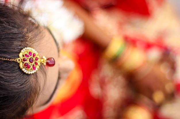 Mariée indienne montrant le style de cheveux de mariage et les bijoux de tête