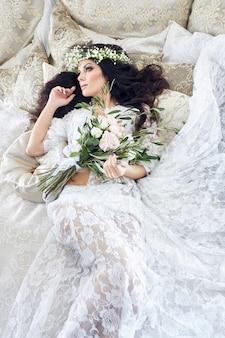 Mariée en lingerie avec une gerbe de fleurs sur la tête