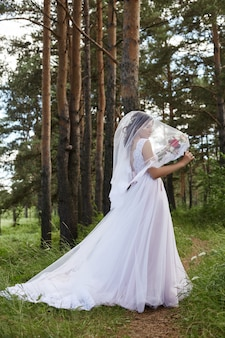 Mariée avec long bouquet haira de fleurs dans ses mains