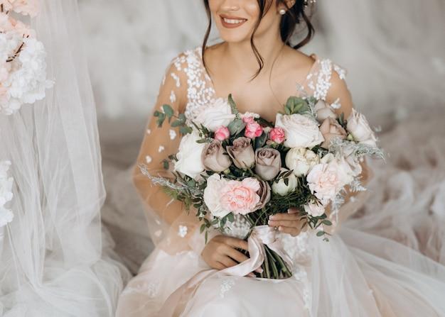 Mariée de luxe tenant un grand bouquet de fleurs