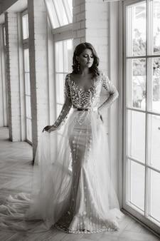 Une mariée luxueuse dans une robe de mariée le matin dans son intérieur. photo noir et blanc.