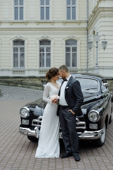 Mariée magnifique élégante et beau marié embrassant dans une voiture noire élégante à la lumière.