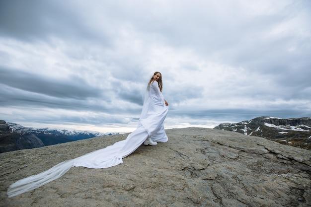 Mariée marchant dans une longue robe de mariée sur un fragment de roche dans les montagnes