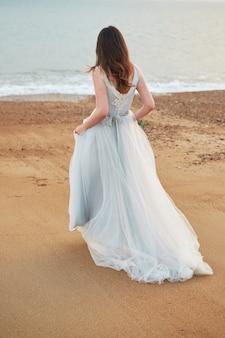 Mariée marchant le long de la côte vêtue d'une belle robe de mariée