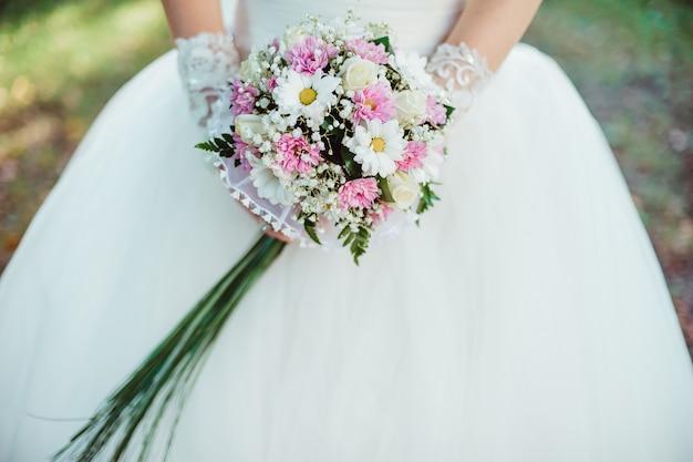 La mariée marche en tenant le bouquet de mariée dans ses mains