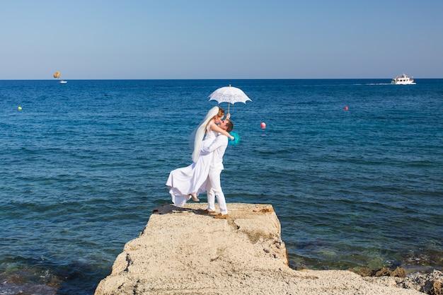 Mariée et marié au bord de la mer le jour de leur mariage