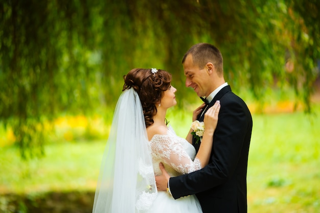 Mariée et le marié au jour du mariage en marchant à l'extérieur sur la nature d'automne. couple nuptial, heureux jeune femme et homme embrassant dans un parc verdoyant. couple de mariage aimant en plein air.