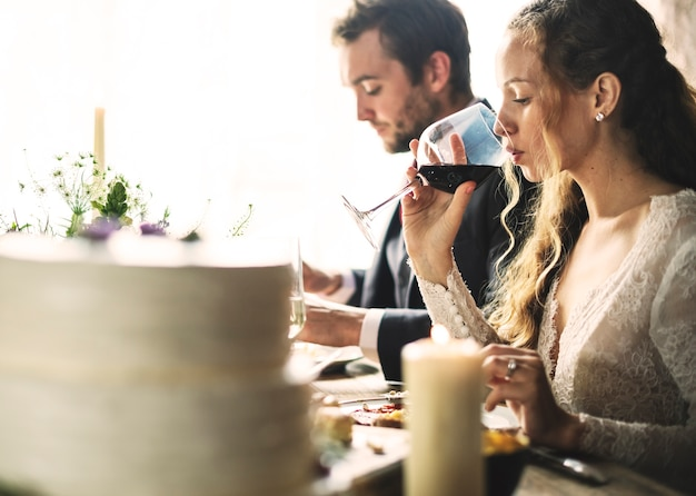 Mariée et le marié ayant des repas avec des amis à la réception de mariage