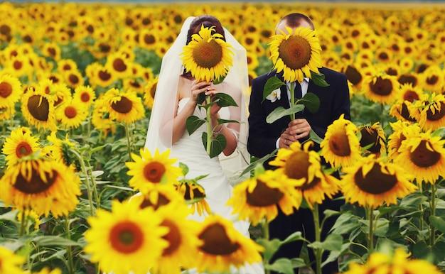 Mariée et le marié cachent leurs visages derrière les tournesols jaunes