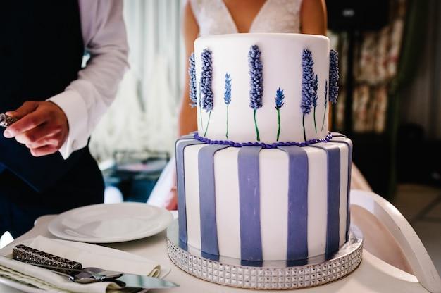 La mariée et un marié coupe un gâteau rustique lors d'un banquet.