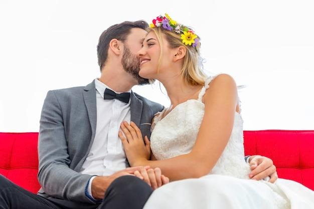 Mariée et le marié couple de baiser caucasien et câlin dans le studio de mariage.