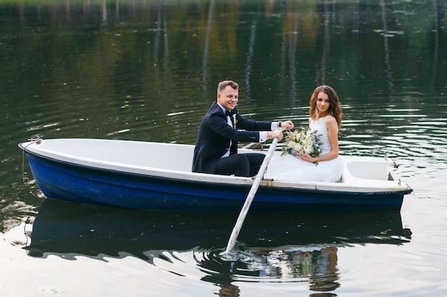 La mariée et le marié dans une barque sur le lac