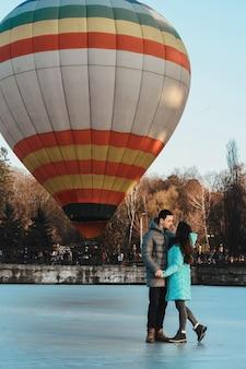 Mariée et marié dans le contexte d'un lac gelé et d'un ballon volant dans un parc de la ville.