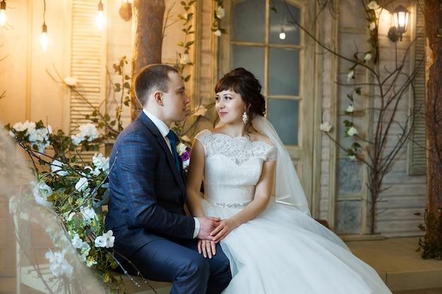 Mariée et le marié dans des vêtements de mariage s'embrassent à la maison. couple amoureux après une cérémonie de mariage