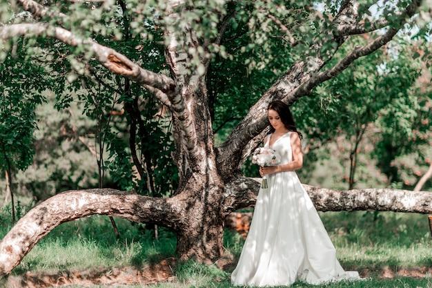 Mariée de marié debout près du vieux grand arbre