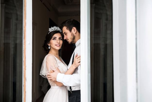 La mariée et le marié debout près d'une grande fenêtre. le couple sourit et rêve.