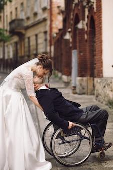 Mariée et le marié sur le fauteuil roulant posent sur la vieille rue européenne