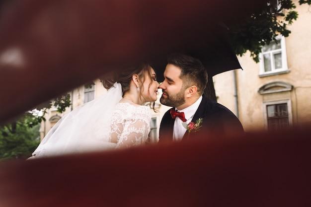 Mariée et le marié sur le fauteuil s'asseoir s'embrasser sur le banc dans le parc