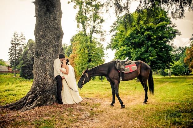 Mariée et le marié heureux à cheval dans la forêt, belle nature