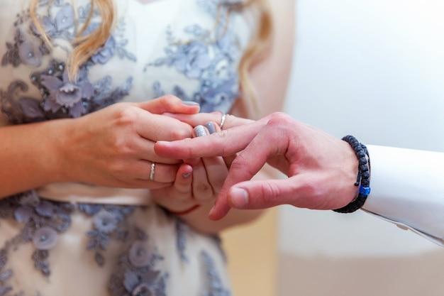 Mariée et marié mains de mariage avec des anneaux de mariage. main de mariée mettant la bague de mariage sur le doigt du marié.