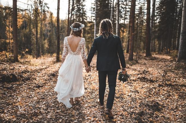 Mariée et le marié marchant sur le sol couvert de feuilles dans les bois pendant la journée