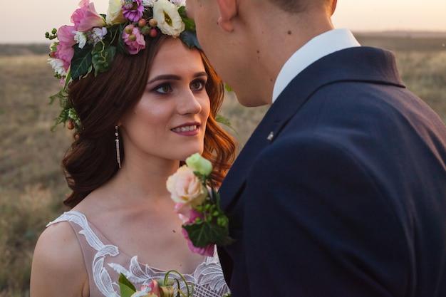 La mariée et le marié marchent au coucher du soleil.